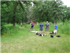 Four men at disc golf stand one throwing