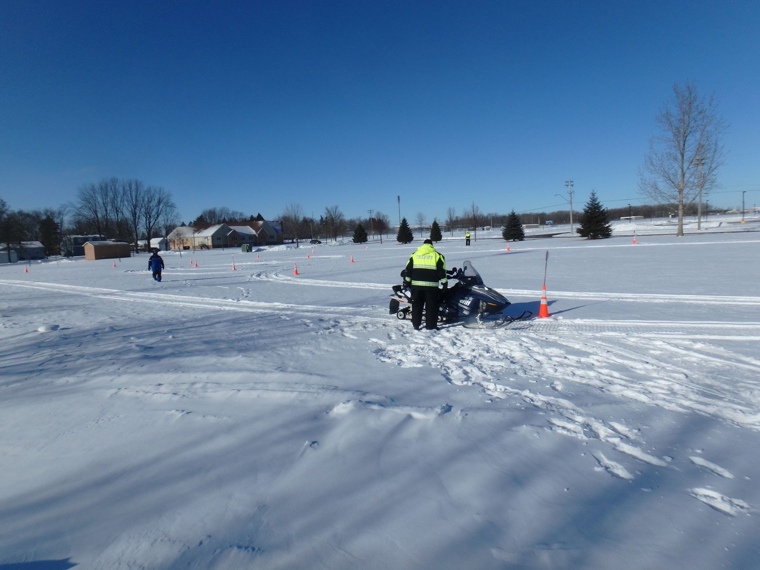 Young person riding snowmobile through safety course